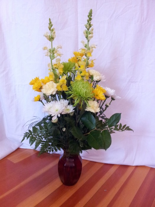 Green, yellow, white flowers in red vase.