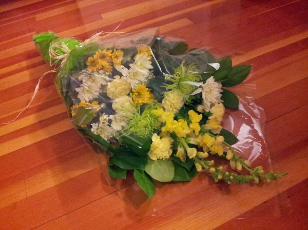 Green, yellow, white flowers wrapped in tissue paper, cellophane.