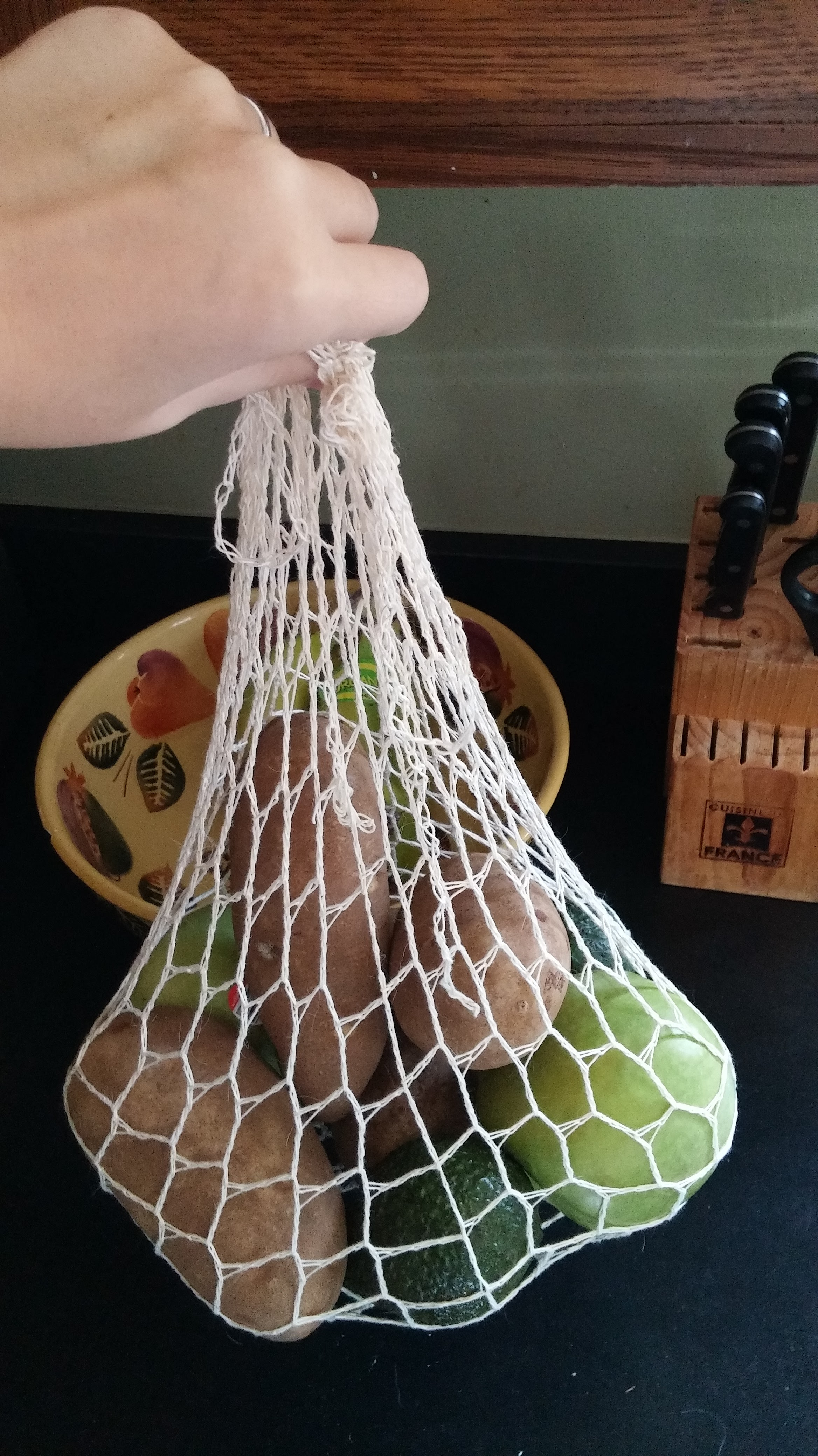 A crocheted produce bag containing 4 russet potatoes, 2 granny smith apples, and 2 small avocados