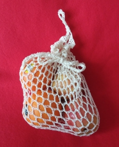 crocheted produce bag filled with two oranges and 2 apples